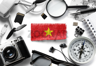 Flag of Vietnam and travel accessories on a white background.