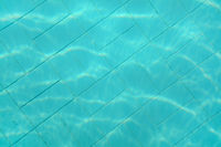 Underwater photo - old swimming pool bottom. Blue tiles pattern visible on floor. Abstract water background.