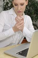 Frau im Büro leidet an Arthritis