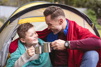 Caucasian father and son smiling while toasting their coffee cups sitting in a tent in the garden