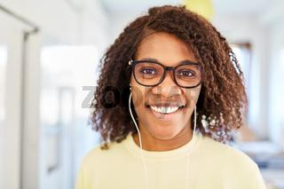 Afroamerikanische Frau mit In-Ear Kopfhörern beim Musik hören