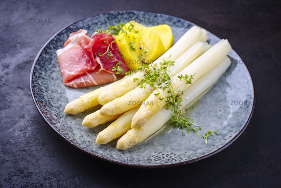 Traditional steamed white asparagus with cured ham and boiled potatoes garnished with butter sauce served as close-up on a Nordic design plate