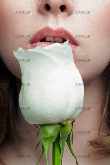 Closeup macro portrait of female face with white rose flower near lips