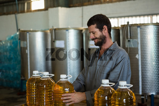 Worker checking a can of olive oil in factory