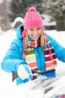 Woman wiping car windshield using brush snow