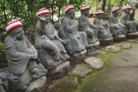 Buddha statues with knitted hat offerings at the temple Diasho-in in Miyajima, Hiroshima, Japan