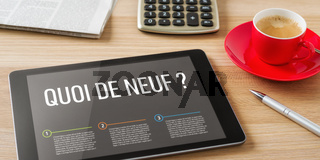 A tablet on a wooden desk - Whats new in french - Quoi de neuf