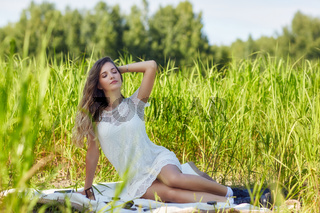 Young blonde woman in white dress is sitting on a picnic sheet in tall grass.