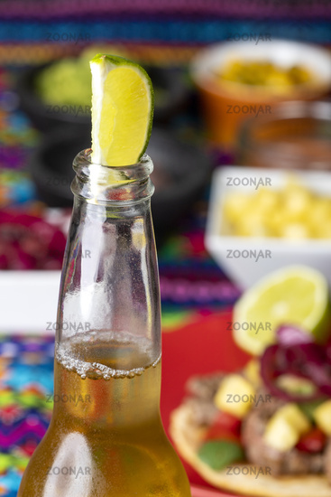 Lime in a beer with Mexican tortilla and salsas