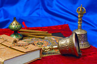two Tibetan ritual bell and a book on a blue backg