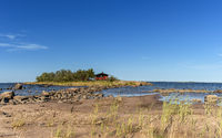 picturesque coastal landscape on the Baltic Sea with a small red cottage on an island behind a sandy beach under a blue sky