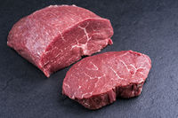Raw dry aged wagyu beef rump steak slice and piece as close-up on black background with copy space