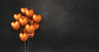 Copper heart shape balloons bunch on a black wall background. Horizontal banner.