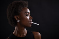 Sexy african american woman smoking cigarette on black background
