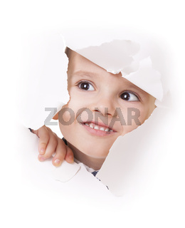 Curious kid looks through a hole in white paper