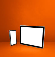 Mobile phone and digital tablet pc on orange office desk