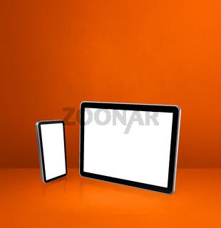 Mobile phone and digital tablet pc on orange office desk