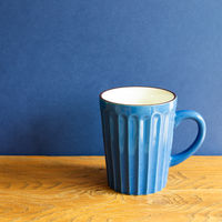 Blue mug cup on wooden table. blue wall background