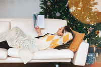Relaxed woman reading book while lying on sofa in living room with decorated Christmas tree