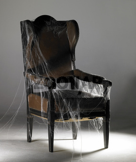 brown wing chair and cobwebs