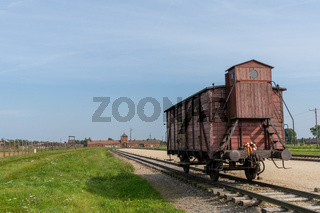 Auschwitz Concentration Camp in Poland with railroad tracks and a wooden carriage for transporting prisoners in the foreground