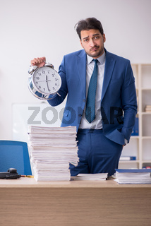 Young male employee in time management concept in the office