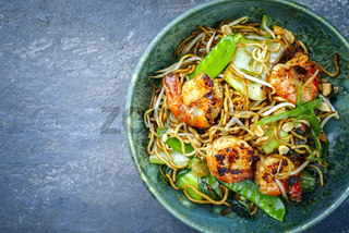 Modern style traditional Thai phak kung curry with barbecue king prawns and noodles as top view in Nordic design bowl with copy space left