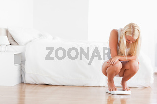 Blonde woman squatting on a weighing machine