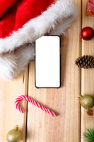 Composition of smartphone with copy space and christmas decorations on wooden background