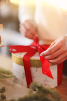 Young girl in white sweater packing round present box tied with bright red ribbon