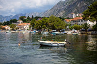 Very beautiful embankment of the Bay of Kotor, a small fishing boat. Montenegro. A beautiful and cozy city, tiled houses. The concept of rest and vacation in Europe.