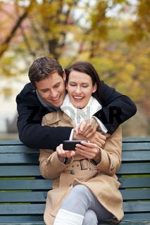 Mann und Frau schauen auf Smartphone