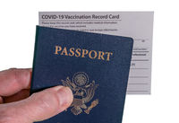 Senior man holding Covid-19 vaccination record certificate and US passport to show immunity to virus for travel