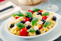 Fresh Pasta Salad with Tomatoes and Black Olives. High quality photo