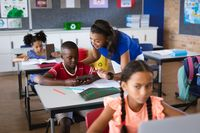 African american female teacher teaching a boy to use digital tablet in class at elementary school