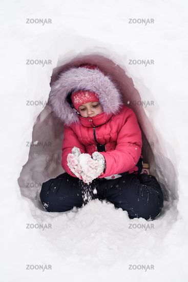 Cute caucasian girl plays with snow in her hiding place. Winter entertainment