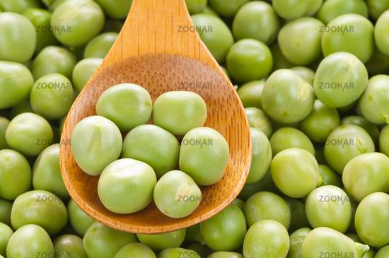 Fresh grren peas on wooden spoon
