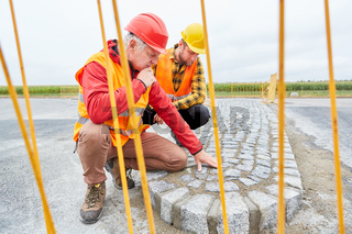 Bauarbeiter kontrollieren Konstruktion der Fahrbahn
