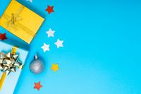 Composition of christmas decorations with presents, baubles and copy space on blue background