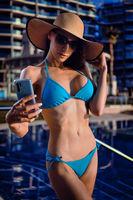 Woman in bikini take selfie near swimming pool