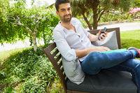 Freelancer im Garten im Sommer mit Smartphone