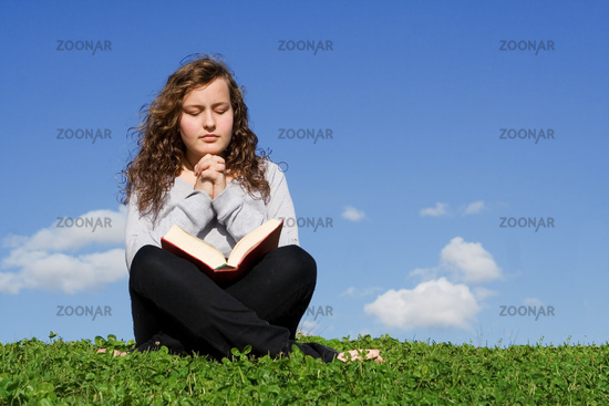 child or teen praying and reading bible outdoors