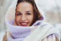 Young woman face covered with light colored knitted scarf