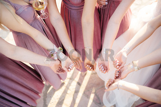 Hands of bridesmaids and bride with drawings on the wrists