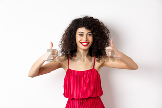Attractive young woman recommending promo offer, showing thumb up and smiling, like product, standing in festive red dress on white background