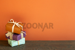 Stack of colorful gift boxes on wooden table. red wall background