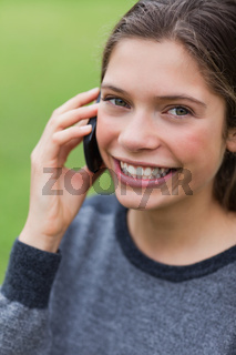 Teenage girl calling with her mobile phone while looking at the camera