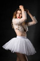 Seductive ballerina in white clothes touching head