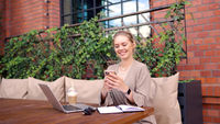 Happy freelancer using smartphone in cafeteria