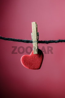 miniature red hearth hanging on clothespins with miniature wood clips